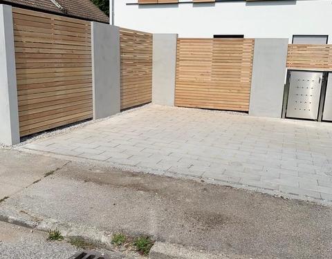 Zaunanlage mit Gartentor und Mülltonnenbox aus Holz und Betonelementen